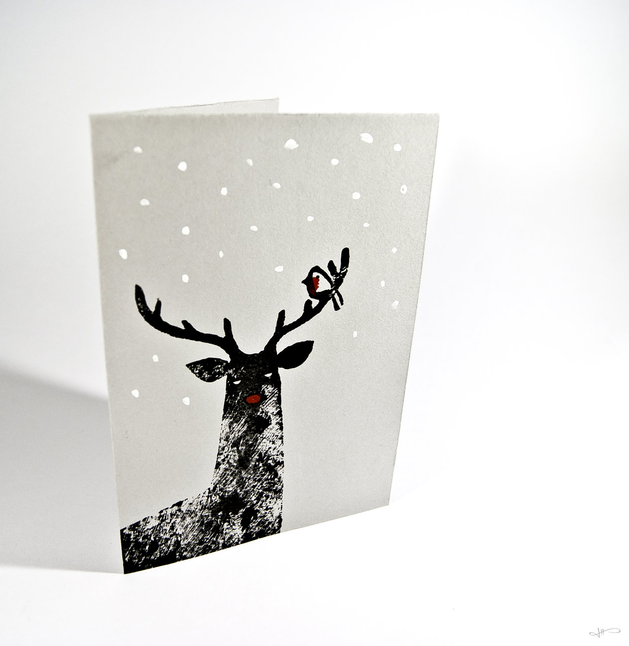Photograph of a linocut reindeer printed in black, with a painted red nose, robin and white snow on grey paper, on a clean white background.